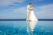 foto of infinity pool  - portrait of a bride and groom kissing on a infinity pool against the sky