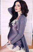 Beautiful Pregnant Woman With  Dark Hair Posing In Silk Dress