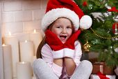 Little girl in Santa hat and mittens sitting near fir tree on fireplace with candles background
