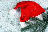 Santa red hat with fir-tree branch and snowflakes on color wooden background