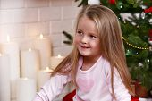 Little girl sitting near fir tree on fireplace with candles background