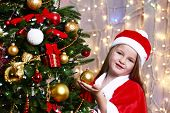 Little girl near Christmas tree on bright background