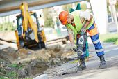 stock photo of boring  - Builder worker with pneumatic hammer drill equipment breaking asphalt at road construction site - JPG