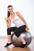 picture of pregnancy exercises  - Pregnant woman is doing exercises with gymnastic ball and dumbbells - JPG