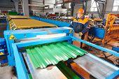 industrial worker operating metal sheet profiling mechine at manufacturing factory