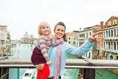 Baby Girl And Mother Poiting While Standing On Bridge With Grand Canal View In Venice, Italy