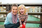 Portrait Of Happy Mother And Baby Girl On Bridge With Grand Cana