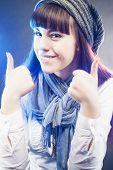 Portrait Of Smiling And Happy Caucasian Girl In Winter Long Hat Showing Thumbs Up In Studio Environm