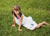 picture of flirty  - Beautiful girl with a flirty smile sitting on the lawn - JPG
