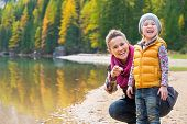 Portrait Of Smiling Mother And Baby On Lake Braies In South Tyro