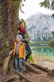 image of south tyrol  - Portrait of mother and baby standing near tree on lake braies in south tyrol italy - JPG