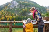 foto of south tyrol  - Mother and baby looking in information board while on lake braies in south tyrol italy - JPG