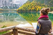 Young Woman With Map On Lake Braies In South Tyrol, Italy. Rear View