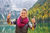 Happy Young Woman On Lake Braies In South Tyrol, Italy Showing Thumbs Up