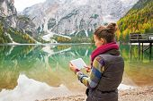 stock photo of south tyrol  - Young woman using tablet pc while on lake braies in south tyrol italy - JPG