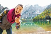 stock photo of south tyrol  - Happy young woman on lake braies in south tyrol italy showing thumbs up - JPG