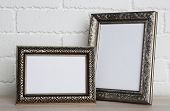 Golden photo frames on wooden surface, on brick wall background