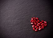 Ripe Pomegranate Seeds In Form Of Heart On Black Slate Background