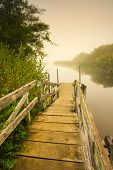 image of dock a lake  - View of a dock that leads to a misty lake on a foggy morning - JPG