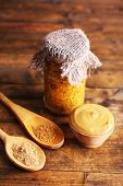 Dijon Mustard in glass jar on wooden background