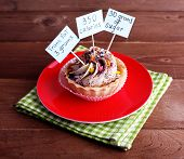 Delicious cake with calories count labels on color plate with napkin, on wooden table background