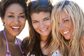 image of blonde woman  - Three beautiful young women in their twenties laughing and having fun at a beach shot in golden evening sunshine - JPG