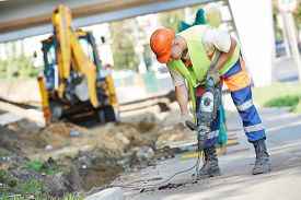 picture of reconstruction  - Builder worker with pneumatic hammer drill equipment breaking asphalt at road construction site - JPG