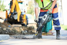 stock photo of reconstruction  - Builder worker with pneumatic hammer drill equipment breaking asphalt at road construction site - JPG