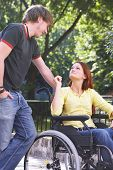 stock photo of rollator  - boy is talking to his girlfriend on a wheelchair - JPG