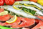 stock photo of redfish  - Large Dish With Fresh Stuffed Fish Salmon Steaks Lemon Slice And Herbs - JPG