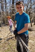 stock photo of spring-cleaning  - Teenager boy and his mother spring cleaning the orchard gathering cut branches to throw them away