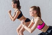 stock photo of squatting  - two girls doing squats together indoors training warm up at gym   - JPG
