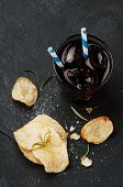 pic of potato chips  - Potato chips and glass of cola on the table selective focus - JPG