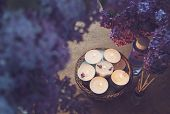 foto of massage oil  - Small white candles in a basket massage oil and essence surrounded by beautiful purple lilac.