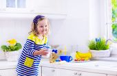 image of little young child children girl toddler  - Little girl preparing breakfast in a white kitchen. Healthy food for children. Child drinking milk and eating fruit. Happy smiling preschooler kid enjoying morning meal cereal with banana and strawberry. ** Note: Shallow depth of field - JPG