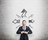 image of directional  - businessman is standing surrounded by arrows in different direction - JPG