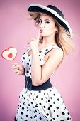 picture of pinup girl  - Young beautiful blonde woman posing in pinup fashionable dress and elegant hat - JPG