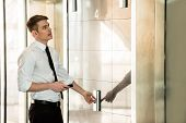 stock photo of elevators  - Young handsome businessman waiting on elevator of an business center - JPG