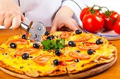 picture of hot fresh pizza  - chef knife cuts fresh hot vegetable pizza - JPG