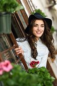 foto of denim wear  - Portrait of young woman smiling in urban background wearing casual clothes and hat - JPG
