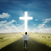foto of worship  - Rear view of young man standing on the road and raise his hands to worship on the GOD - JPG
