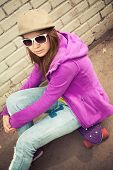 picture of snickers  - Blond teenage girl in cap and sunglasses sits on her skateboard near urban brick wall vertical photo with warm retro tonal correction effect instagram old style filter - JPG