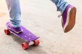 stock photo of snickers  - Feet of a riding skateboarder in jeans and gumshoes - JPG