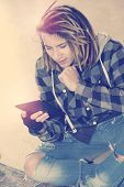 picture of dreadlocks  - freelance dreadlocks guy sitting with digital tablet typing message warm filter applied - JPG