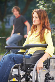 stock photo of rollator  - lonely girl is sitting on a wheelchair on the street - JPG