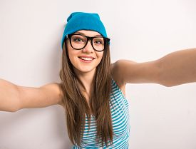 stock photo of selfie  - Beautiful young woman is making selfie standing against grey background - JPG