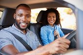 Young black couple in a car on a road trip smiling to camera poster