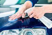 Happy young man looking at camera while waxing a blue car outdoors at car wash poster