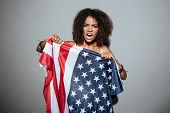 Young african woman screaming and trying to tear apart USA flag and looking at camera isolated over  poster