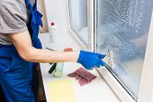 Close-up Of A Man In Uniform And Blue Gloves Washes A Windows With Window Scraper. Professional Home poster